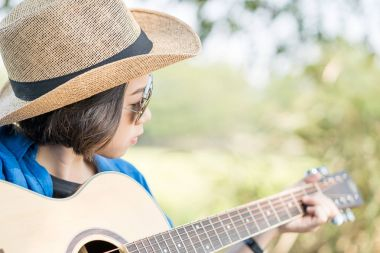 Close up woman wear hat and playing guitar