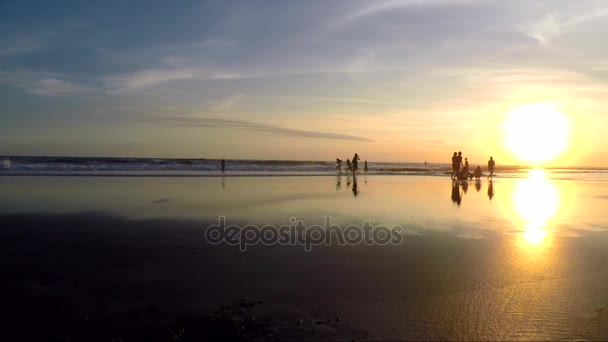 View of people having fun on beach during sunset