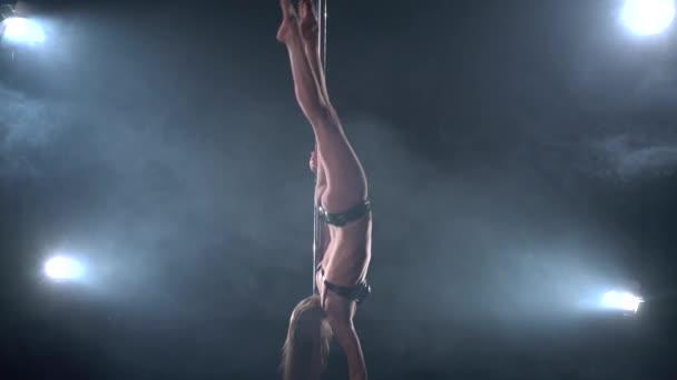 Beautiful athletic woman in pole dance studio