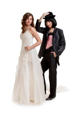 Female gay couple dressed like groom and bride standing