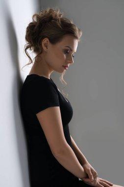 Pretty blonde in black sexy tshirt studio portrait