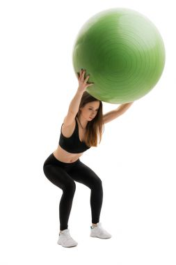Woman with a fitball in studio isolated shot