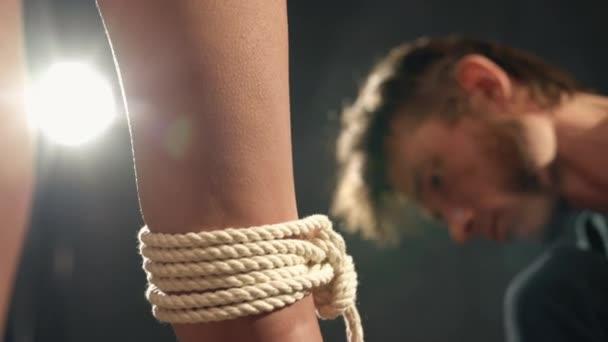 Shibari Kunst Meister Seil um Mädchen Arm binden