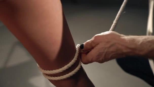 Shibari Art Master bindet Seil um Mädchen Knöchel