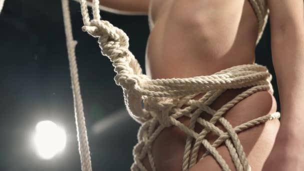 Shibari-Meister knüpft Knoten zum Aufhängen an der Taille