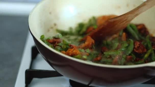 Koch, grüne Bohnen mit Hühnerfleisch in Soja-Sauce rühren