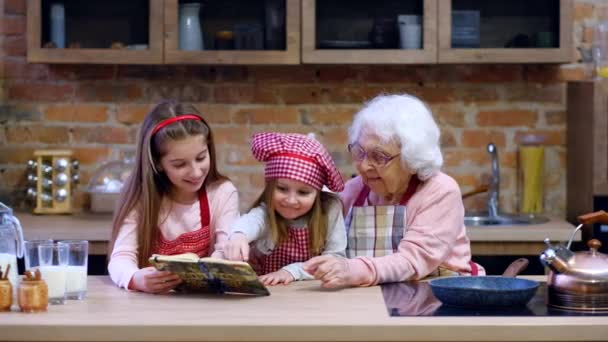 Granny with two granddaughters reading recipe