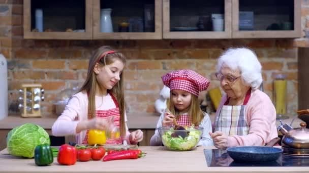 Sestry pomáhají babička připravit salát