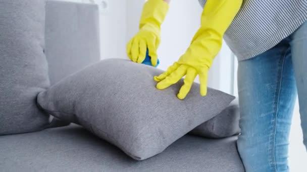 Kissen wird von den Händen in Handschuhen gereinigt