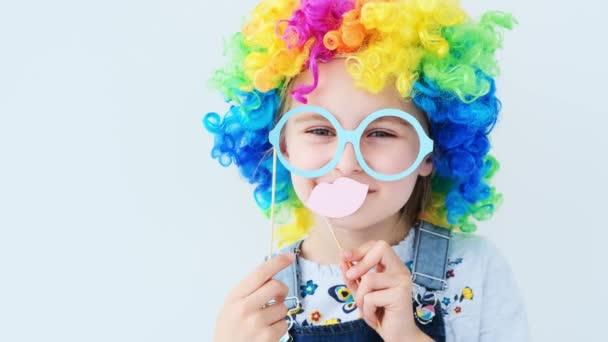 Szép lány, színes parókában, szemüveget és ajkakat tart.