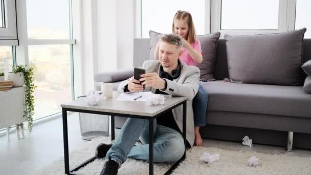 Dívka dělá účes na zaneprázdněný táta