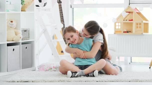 Beautiful smiling sisters happily hugging