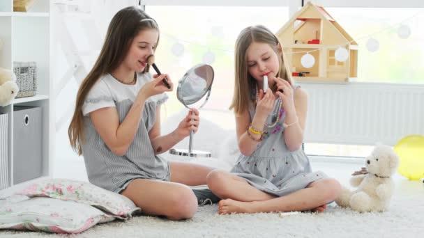 Happy kids girls painting lips