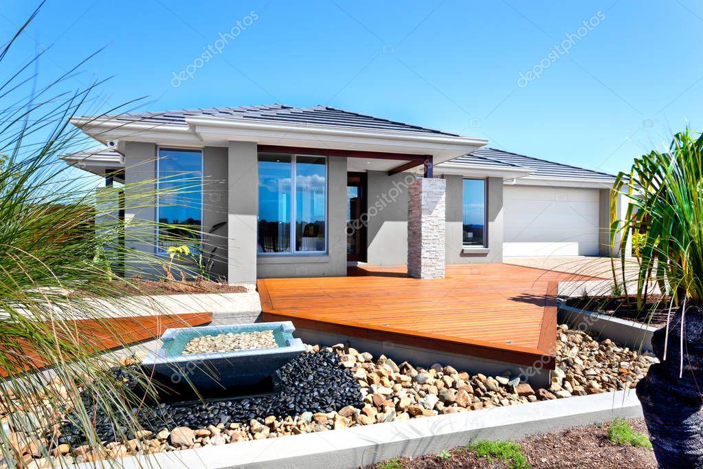 Modern huis met bomen en stenen decoratie items waaronder een s