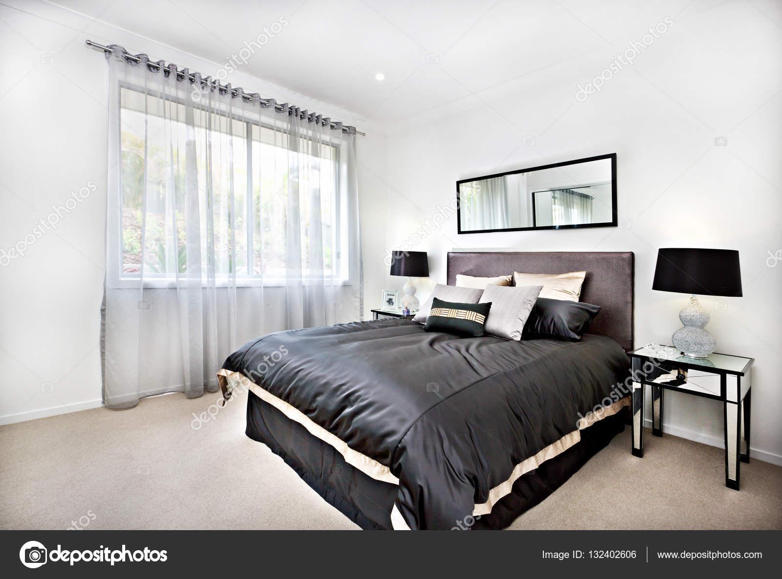 Camera da letto moderna con decorazione nera e specchio accanto ...