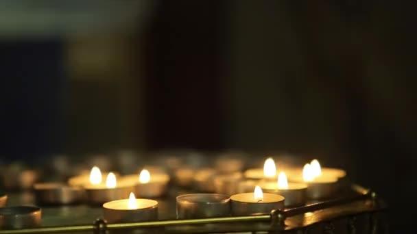 Mnoho svíček plameny zářící ve tmě kostel