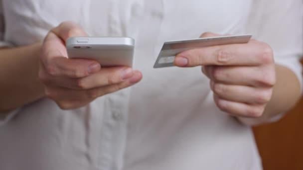 Hände mit Kreditkarte und Mobiltelefon