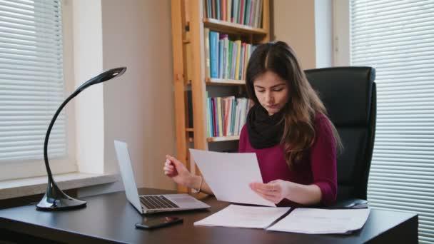 Vážné mladá žena při pohledu na dokumentech
