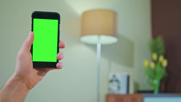 Ruce drží telefon s zeleno -černá obrazovka