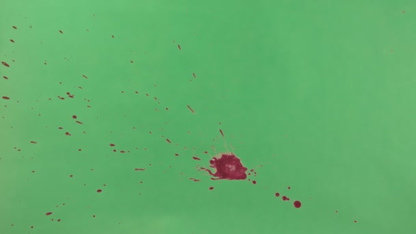 Červený inkoust postříkat nad zelené pozadí