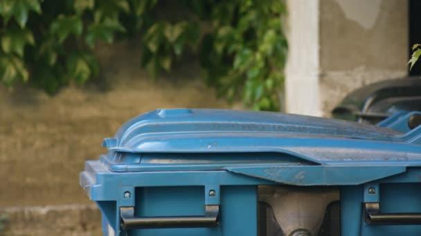 Mladý muž v červených sportovní oblečení vyhodit odpadky