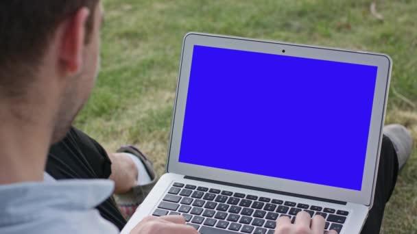 mladý muž pomocí notebooku venku