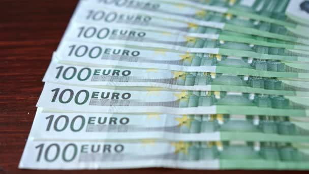 Táplált halom száz Euro-bankjegyek az asztalra