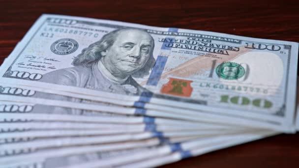 Táplált halom száz dollár-bankjegyek az asztalra