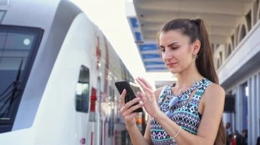 Young Lady Using a Smartphone at Railwaystation.