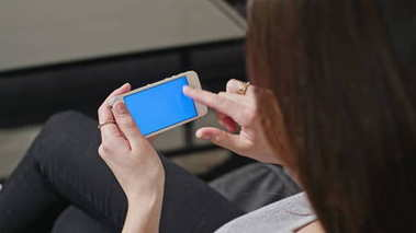 Woman is Holding Smartphone with Blue Screen