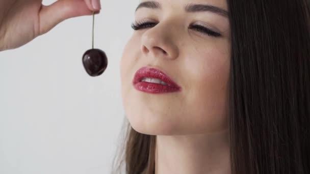 Lány eszik a cseresznye és a meggy. Piros ajkak. Lassú mozgás