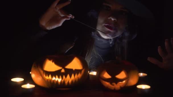 Halloween čarodějnice s magic Pumpkin. Krásná mladá žena v klobouku čarodějnice a kostýmu drží vyřezávané dýně. Umění design Halloween