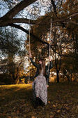 Egy lány lovaglás egy hinta, egy őszi parkban naplementekor