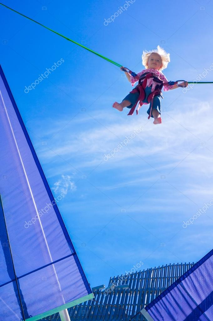 Little blond girl jumping on the trampoline