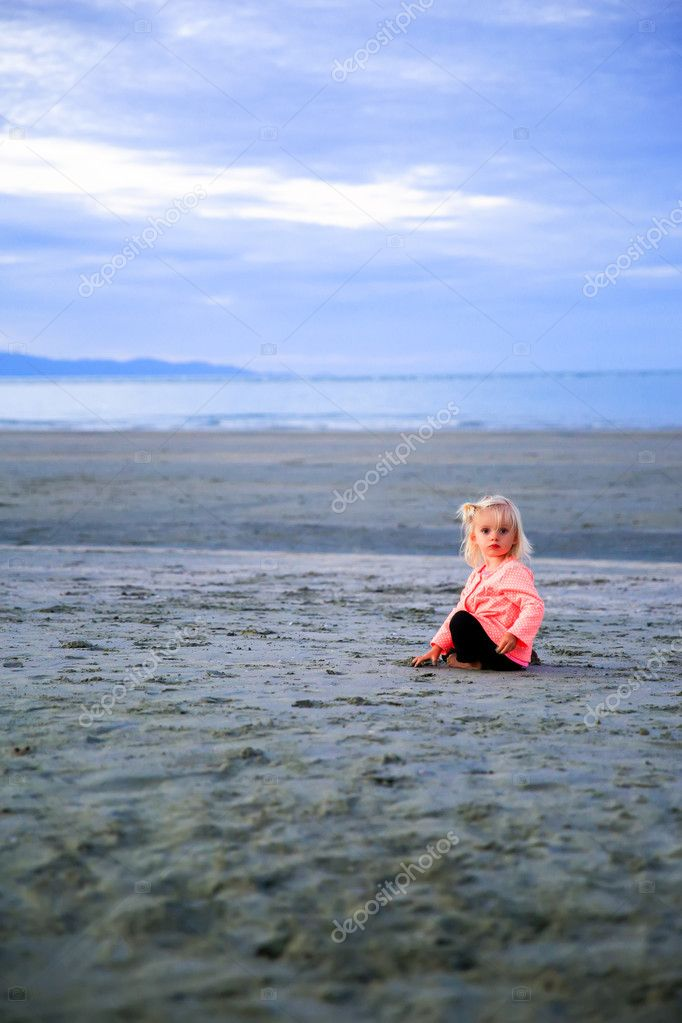 Beautiful blond-haired girl sitting on the beach , playing with sand.