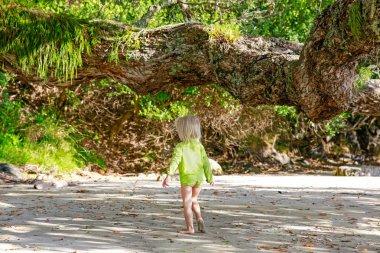 Little blond girl in green shirt walking on sandy Hahei Beach