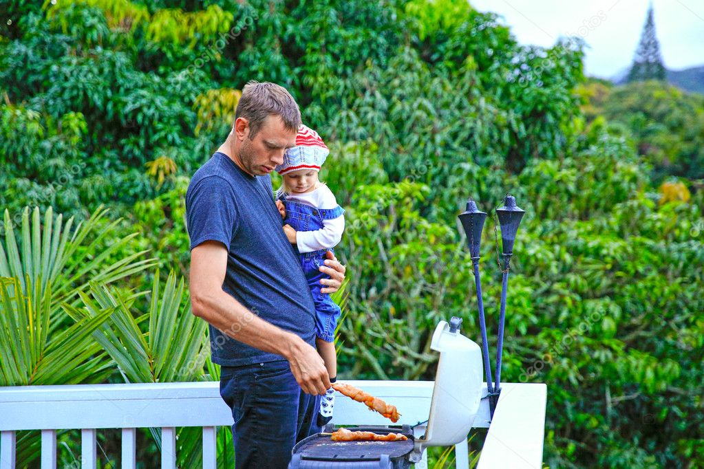 Young loving father and his cute daughter grilling meat