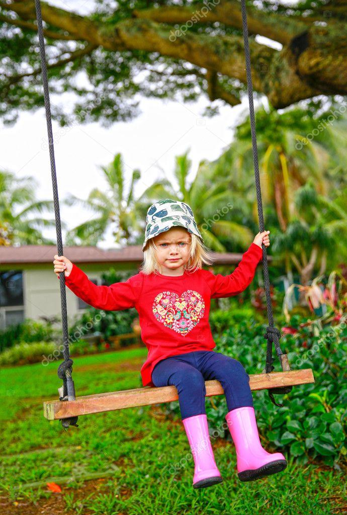 Cute little upset girl swinging on wooden swing outdoors