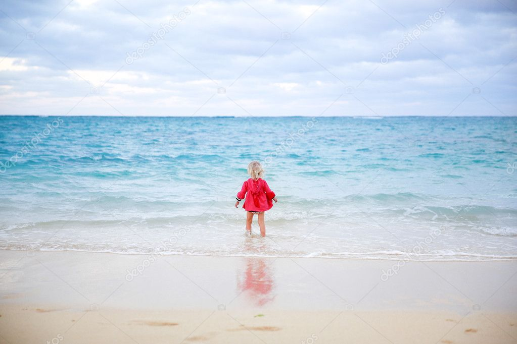 Little girl in red coat staying in the water on the beach