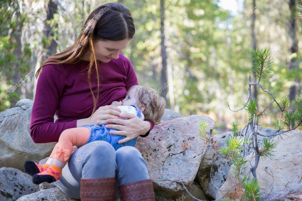 Young mother breastfeeding her baby outdoors