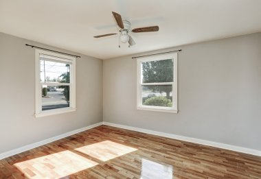 Sunny unfurnished room with hardwood floor in old empty house