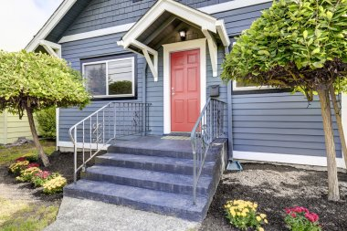 American house exterior in blue color with red front door