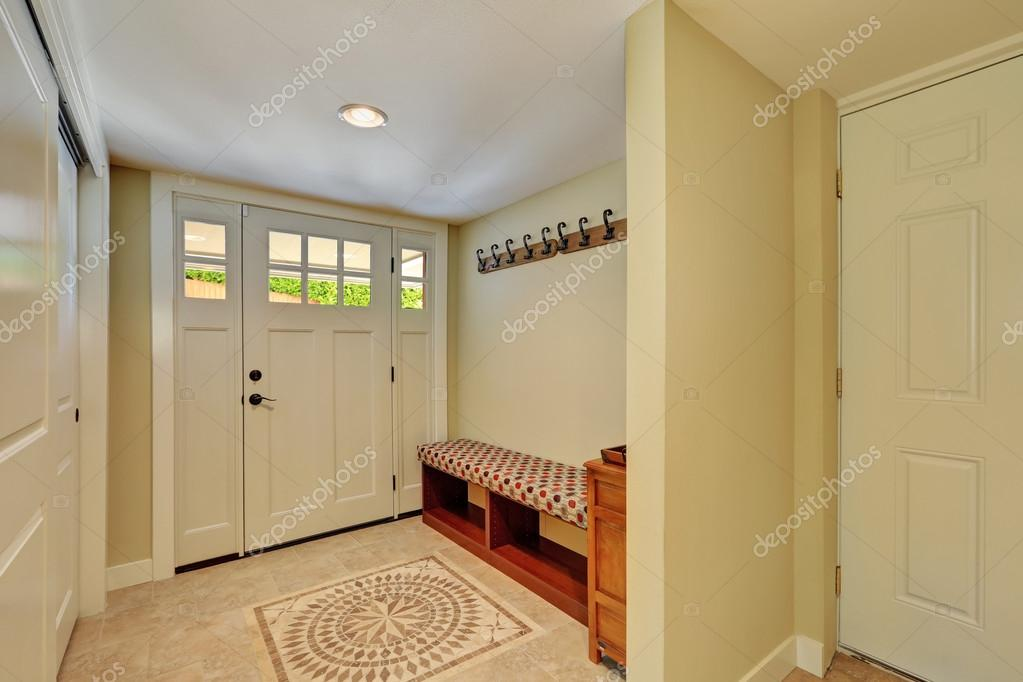 Ingresso in tonalità chiare con pavimento di piastrelle di mosaico