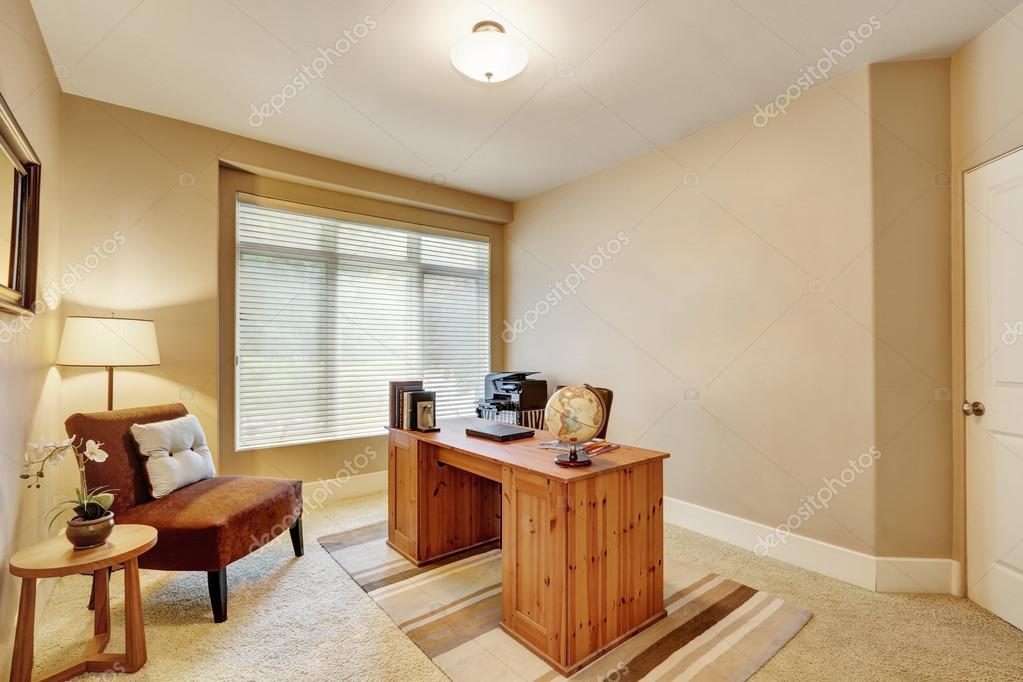 Interieur van kantoor aan huis met beige muren en houten bureau
