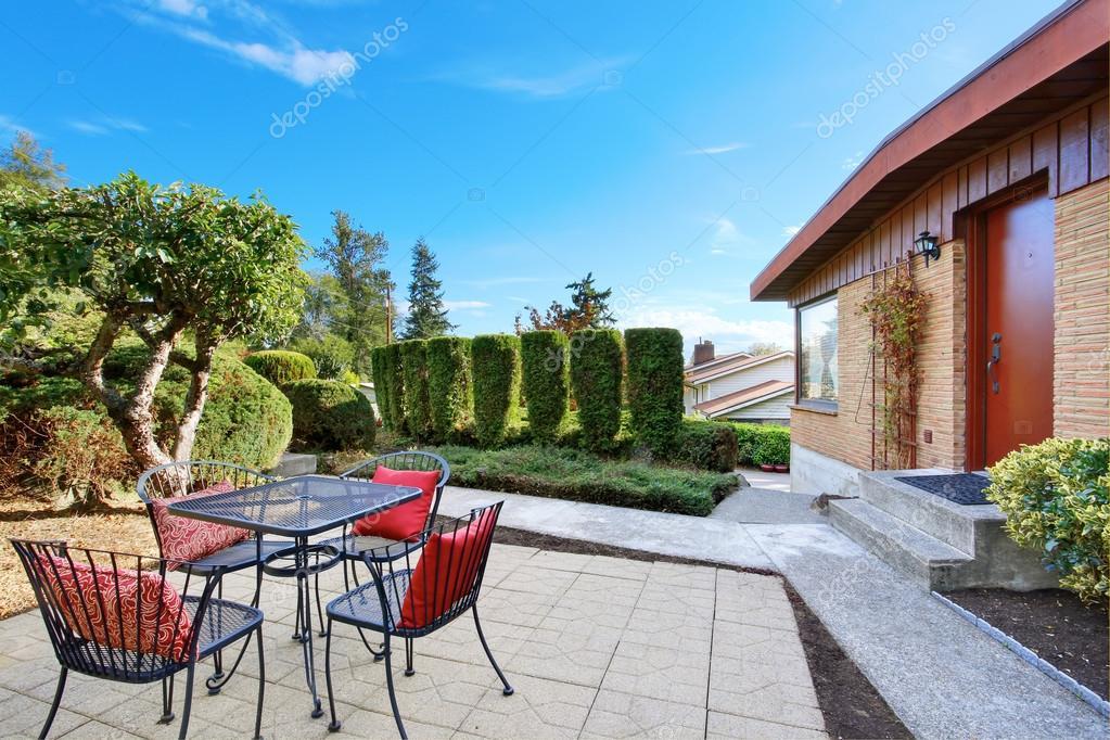 Außenseite der eingeschossige rote Backsteinhaus mit Terrassentisch ...