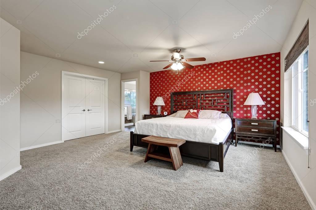 Interno camera da letto matrimoniale con grande letto e parete rossa ...