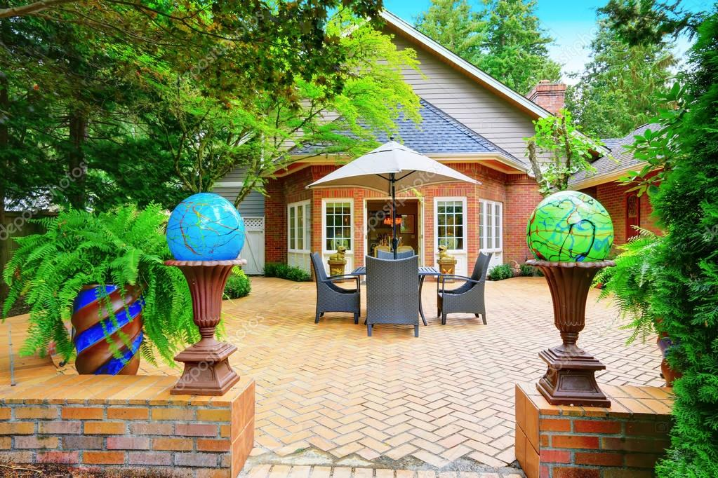 Luxury Red Brick House Exterior. Paved Patio With Globe Lights U2014 Stock  Photo #130424356