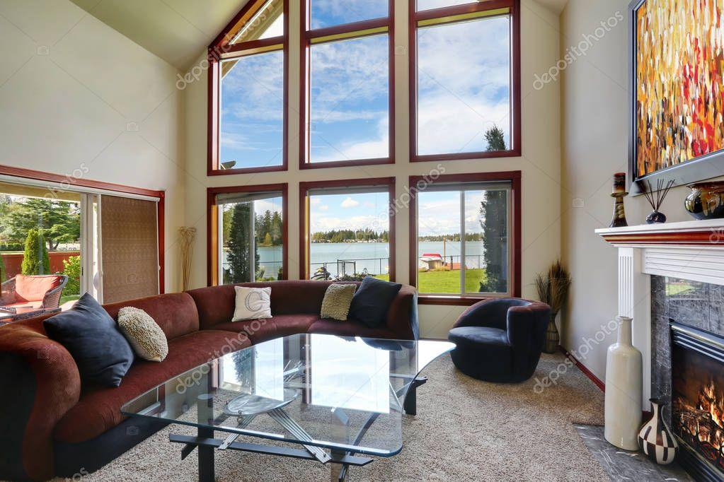 Amerikaanse woonkamer met hoge gewelfde plafond en water uitzicht ...