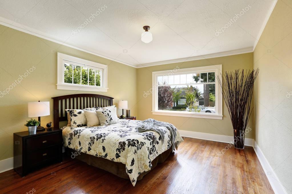 gezellige slaapkamer interieur queen size bed met floral patroon dekbedden aanwezig kamer is ingericht met hoge droge takken in glas vaze staande in de
