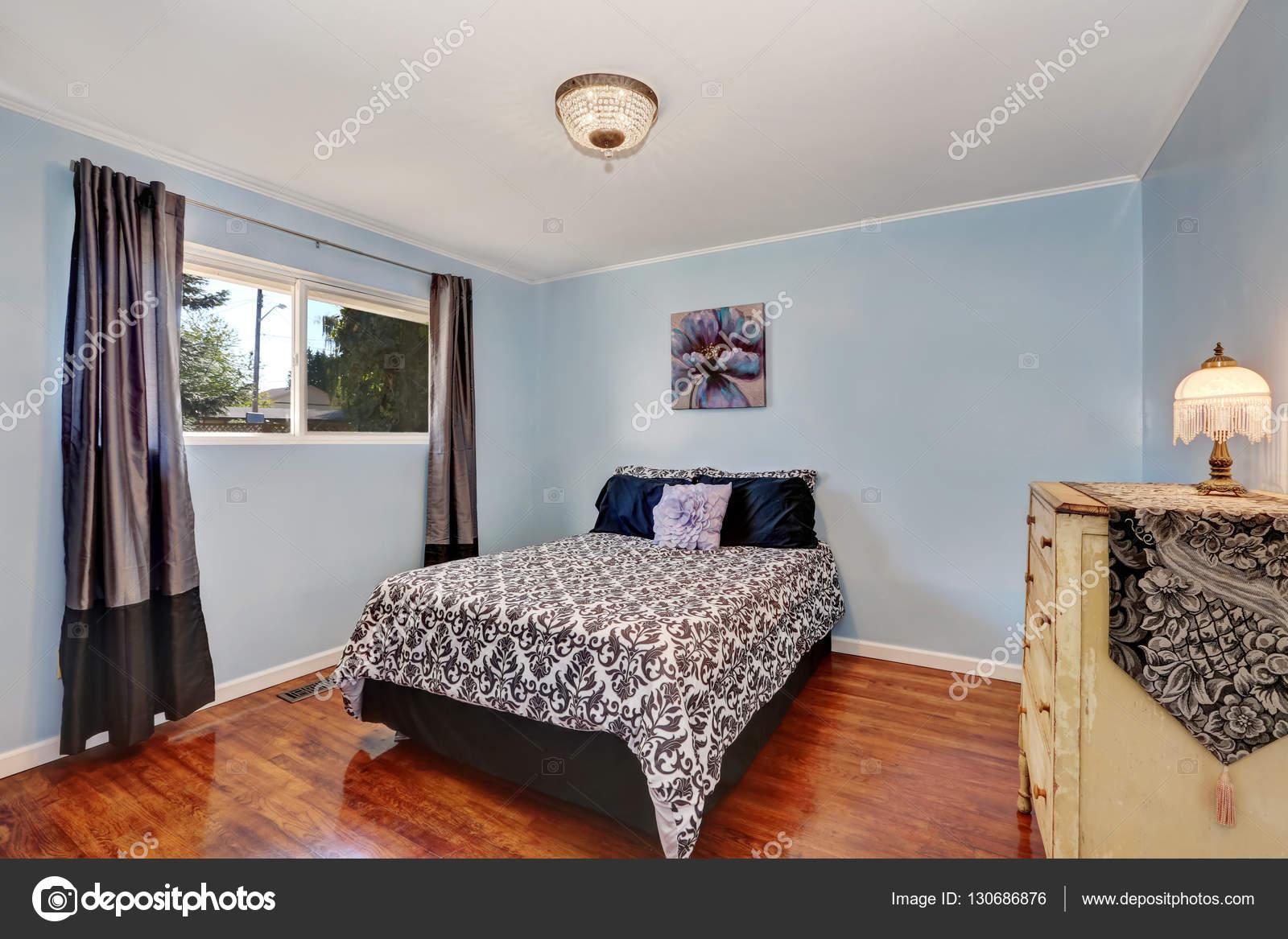 Camera da letto pareti blu con comò antico e pavimenti in legno ...